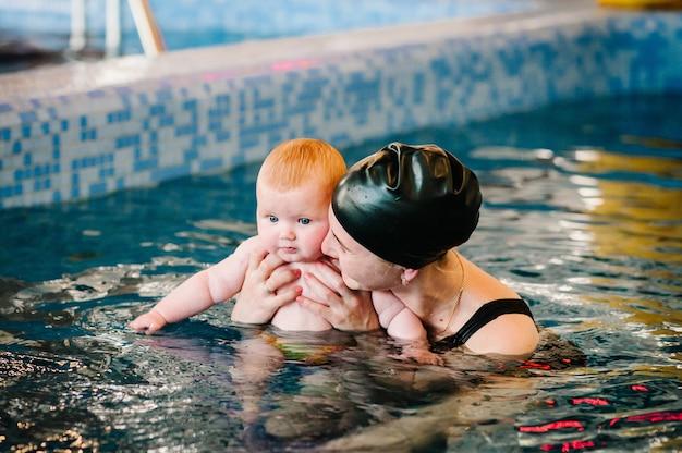 Дайвинг малыш в детском бассейне. мать, инструктор по плаванию и маленькая девочка в бассейне. научите маленького ребенка плавать. наслаждайтесь первым днем купания в воде. мать с ребенком на руках