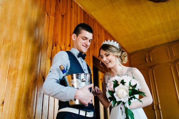 Стильный счастливый жених с бабочкой держит ведро, ведро со льдом и шампанское.
