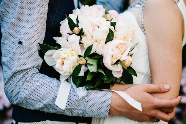 スタイリッシュな花嫁、牡丹と新郎の花束を持つ女性、男。新婚夫婦が抱いています。