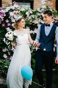 クラウンと新郎の牡丹の花束とスタイリッシュな幸せな花嫁。