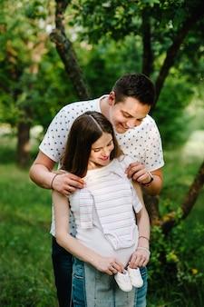 Беременная девушка и муж держатся за руки, чтобы обнять