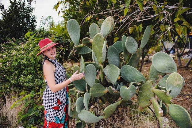 Довольно стройная молодая девушка в красной шляпе и платье. женщина стоит возле кактуса. турция. отдых. отпуск.