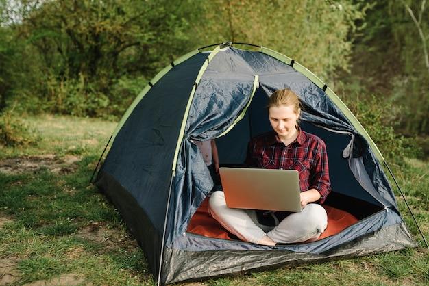 Женщина работает на ноутбуке в палатке в природе