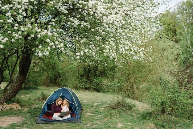 自然の中でテントの中でノートパソコンでオンラインで家族や親戚と通信する