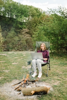 Женщина работает на ноутбуке онлайн на природе. молодой фрилансер отдыхает в лесу