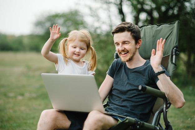 Отец работает в интернете с ребенком на улице