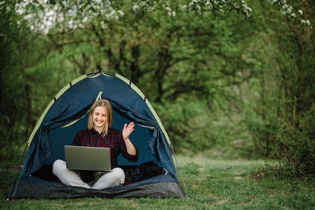 Общайтесь с родственниками, семья онлайн на ноутбуке в палатке на природе