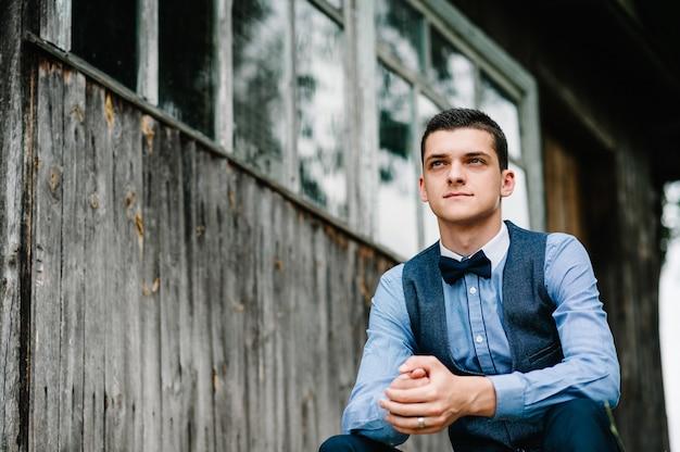 Портрет молодого красивого человека, сидящего рядом с деревянной стеной старого дома