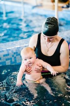 Молодая мама, инструктор по плаванию и счастливая маленькая девочка в бассейне
