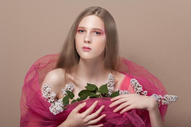 Молодая девушка в розовой вуали с цветами