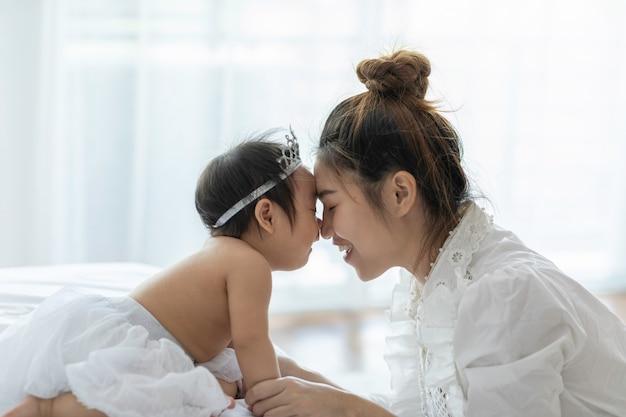幸せな美しさの母持株かわいい甘い愛らしいアジアの赤ちゃんは笑みを浮かべて、居心地の良い寝室、健康な赤ちゃんの概念、セレクティブフォーカスで感情的な幸福と遊ぶ白いドレスを着て