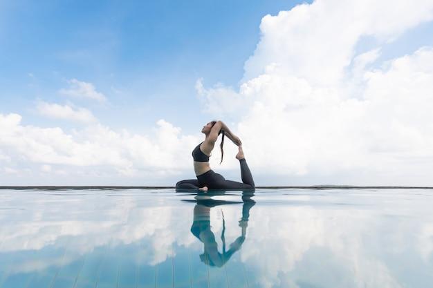 Каникулы привлекательной азиатской женщины, отдыхающей в позе голубя короля йоги на бассейне над пляжем с красивым морем на тропическом острове, чувствуя себя комфортно и расслабляясь в отпуске