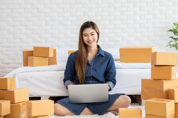 自宅でオンラインショッピングのためのラップトップで働く若いアジア女性の中小企業家