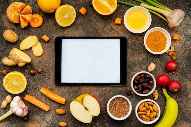 免疫力を高めるために健康食品の周りに白い画面のタブレット。トップビュー、コピースペース。