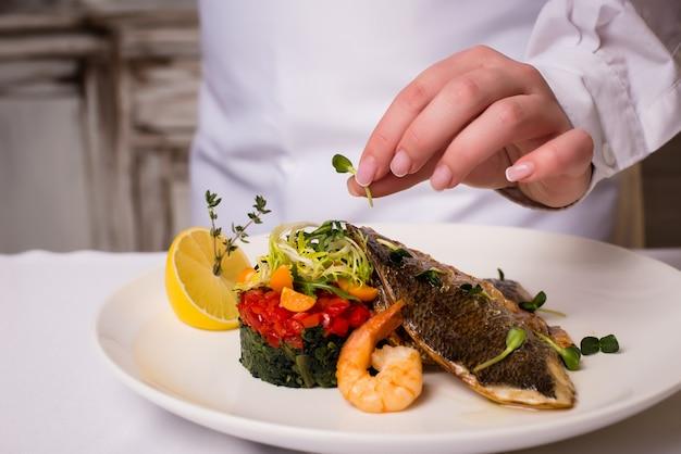 魚料理を提供するレストラン。魚介類、女性の手を調理します。テキスト用の空きスペース。