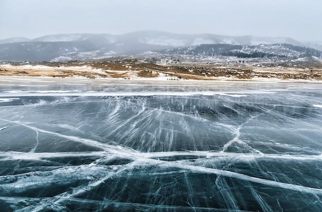 凍ったバイカル湖。凍るような日に氷の表面近くの美しい山。