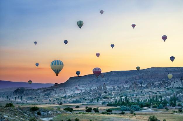 カッパドキアトルコの岩の風景の上を飛んで、熱気球