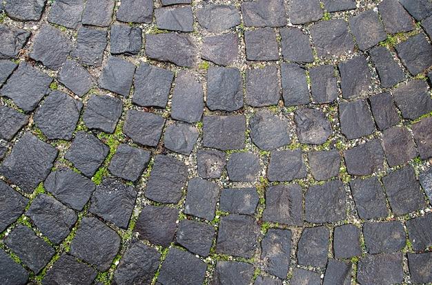 Текстура каменной мостовой. гранитный булыжник фон. конспект старого конца-вверх булыжника. бесшовные. прага