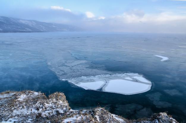 Льдины плывут по воде тумана в озере байкал. закат солнца