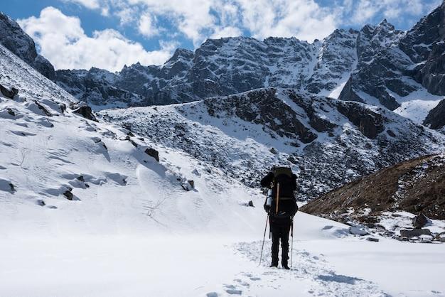 バックパックを持つ男性は、太陽の日に山の頂上に行きます