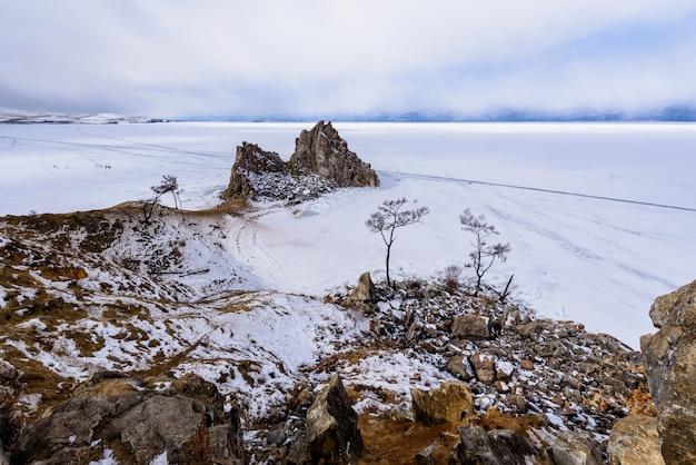 Мыс бурхан на скале шаманка на острове ольхон в солнечный день марта. байкал с красивыми облаками