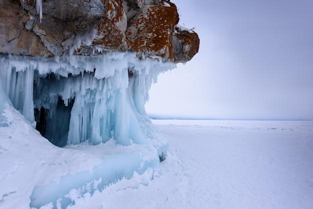 つららで覆われた岩。曇りの天候でバイカル湖。