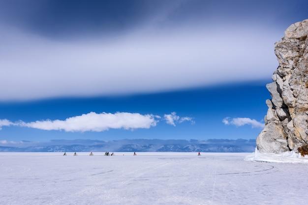 Группа людей едет на велосипеде по замерзшему озеру байкал у мыса бурхан в солнечную погоду с красивыми облаками небом