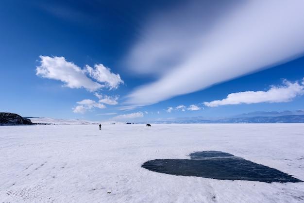 Замерзшее озеро байкал, покрытое снегом и очищенное от снега в форме сердца. красивые слоистые облака над поверхностью льда в морозный день.