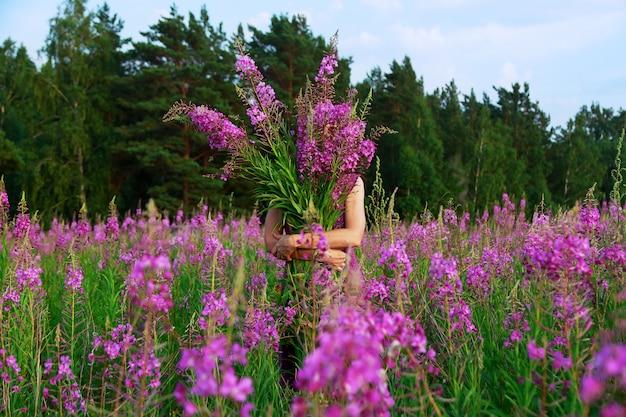 フィールドにピンクの花の花束を保持している若い女性を笑顔