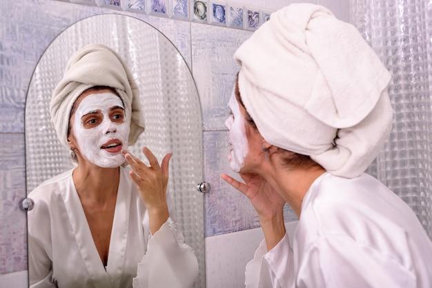 自宅でパジャマで美しいブルネットの女性と彼女の頭の上のタオルがバスルームで彼女の顔に白いマスクを置く