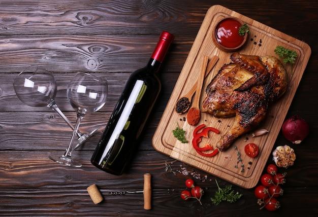 Жареные куриные ножки со специями и овощами, с бутылкой красного вина.