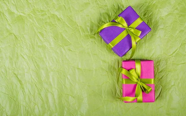 しわくちゃの紙の背景に明るいギフトボックス。お祭りの背景。紙の背景