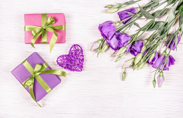 Подарки и цветы. коробки с подарками и букет цветов эустома на белом фоне. плетеное сердце. романтическая концепция.