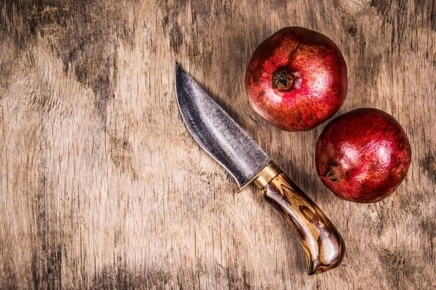 Две спелые гранаты и нож на деревянной доске