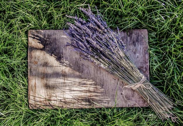 Букет из ароматной лаванды на деревянный стол. деревянный стол на зеленой траве.