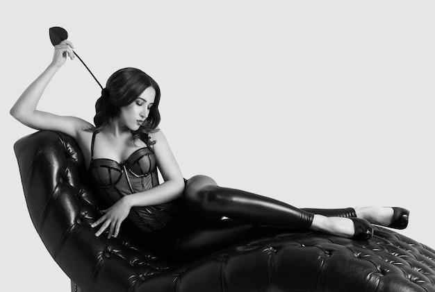 セクシーなエレガントな女性は革のソファのコルセットにあります。