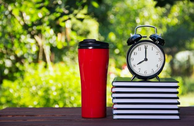 本、サーモマグ、目覚まし時計のスタック。
