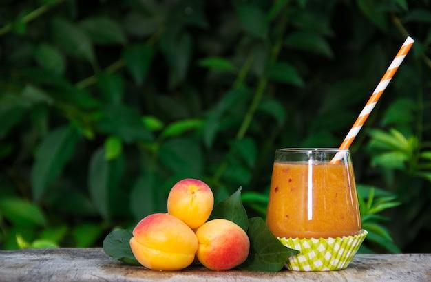 Освежающие абрикосовые смузи и спелые абрикосы в летнем саду