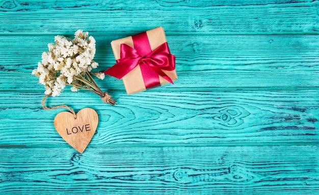 サテンリボン、花、青い木製の背景にハートのギフトボックス。お祝いのコンセプトです。コピースペース