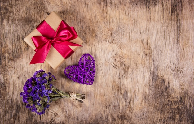 サテンリボン、枝編み細工品の心、古い木製の背景の花のギフトボックス