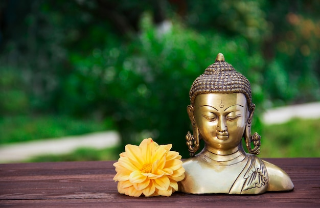 Золотая античная статуя будды на размытом зеленом фоне.