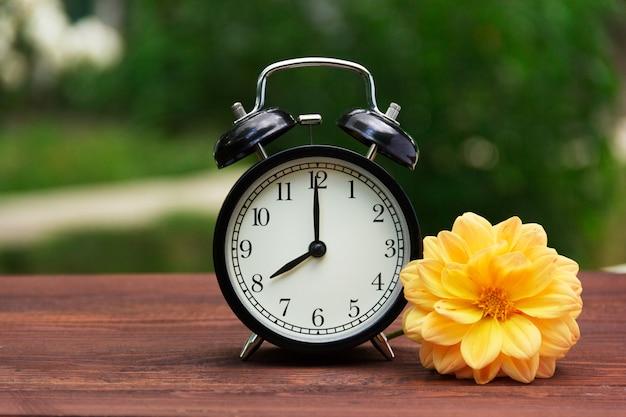 テーブルの上の庭でクラシックな黒の目覚まし時計