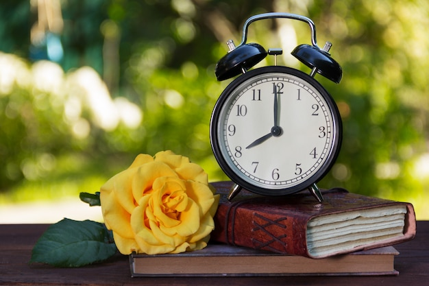 古い目覚まし時計、書籍のスタック、木製のテーブルのバラ