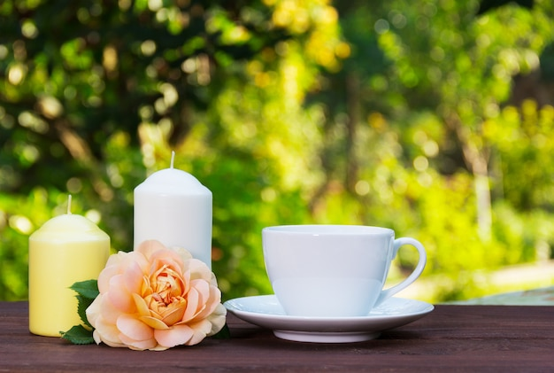 Чашка горячего чая в саду, ароматные розы и свечи