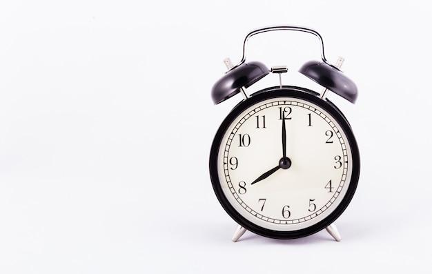 白の背景に黒の古典的な目覚まし時計。黒い時計。コピースペース