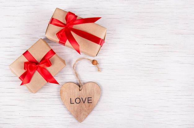 Две маленькие подарочные коробки с красными лентами и валентинкой ручной работы на белом деревянном фоне