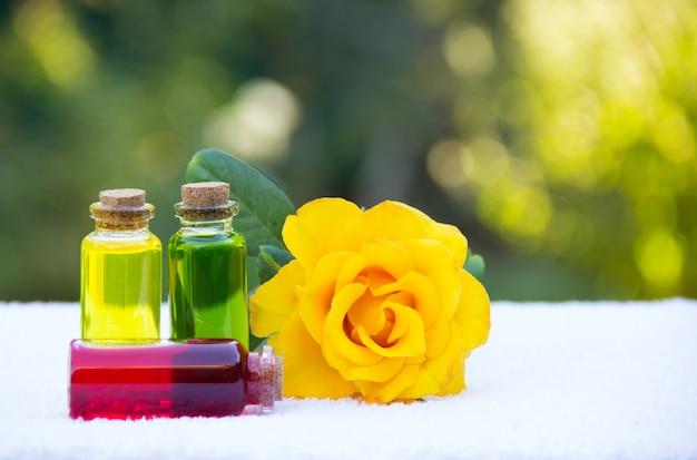 Ароматные натуральные цветочные масла в бутылочках и желтая роза
