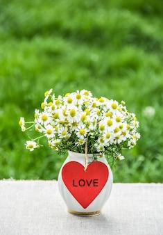 花瓶と赤いハートのフィールドカモミールの花束