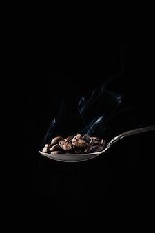 Макрофотография выстрел из кофейных зерен в ложку с дымом на темном