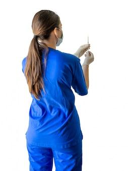 Молодой женский кавказский доктор в медицинской форме и перчатки подготавливая шприц для впрыски